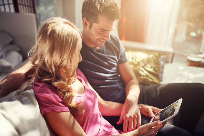 attractive couple using tablet together o nfuton h at home
